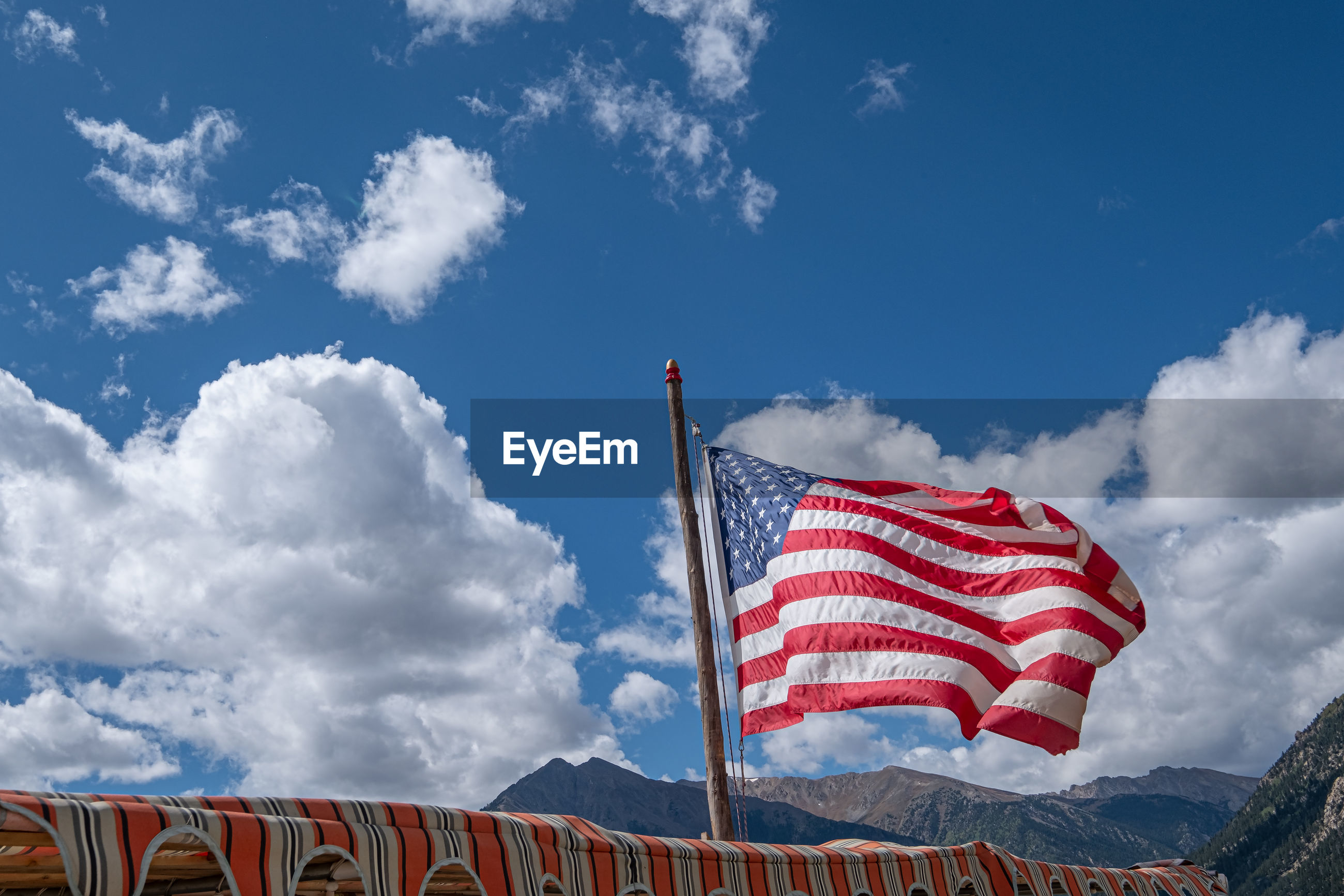 American flag in wind against clouds and blue sky