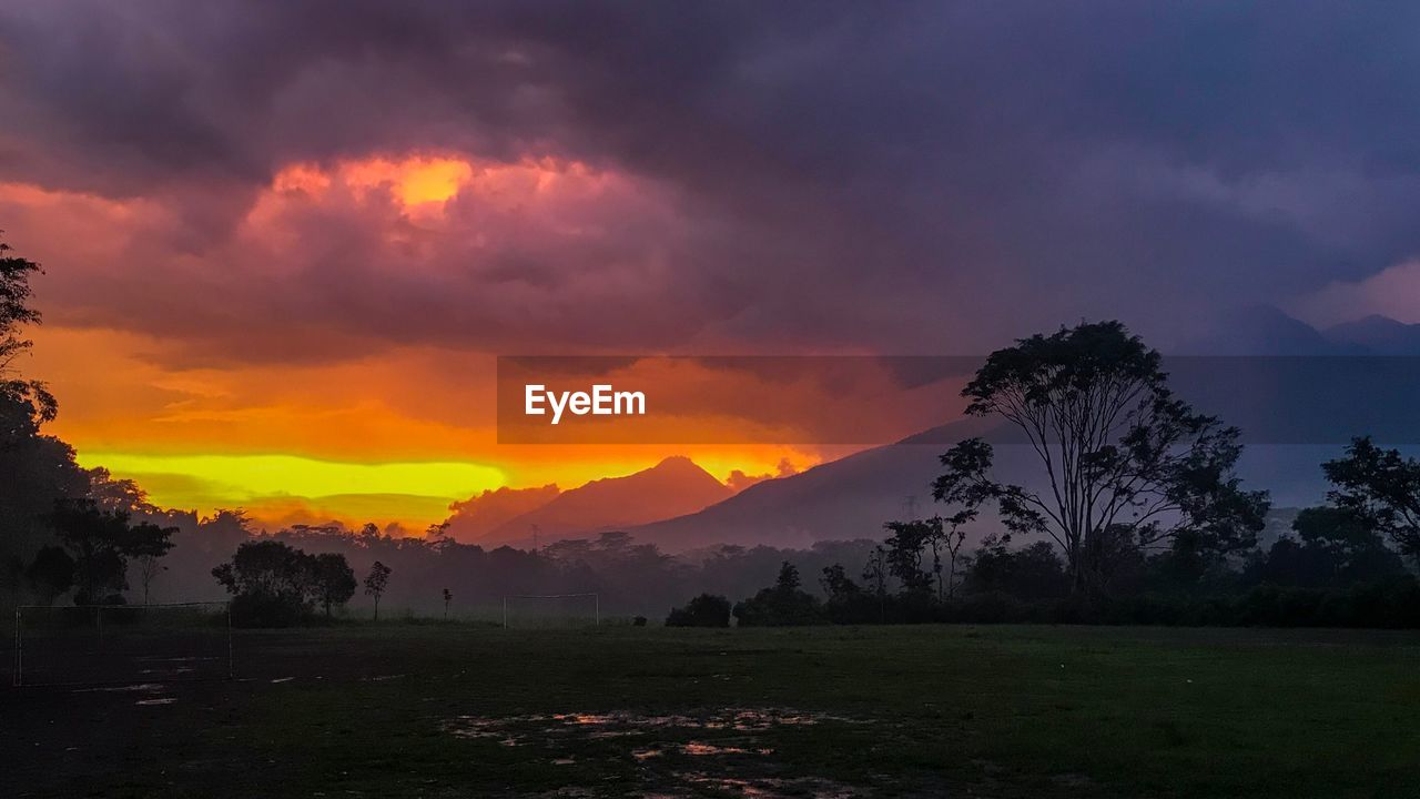 sky, beauty in nature, cloud - sky, scenics - nature, sunset, tree, tranquil scene, tranquility, environment, plant, nature, landscape, non-urban scene, land, idyllic, no people, field, mountain, orange color, outdoors