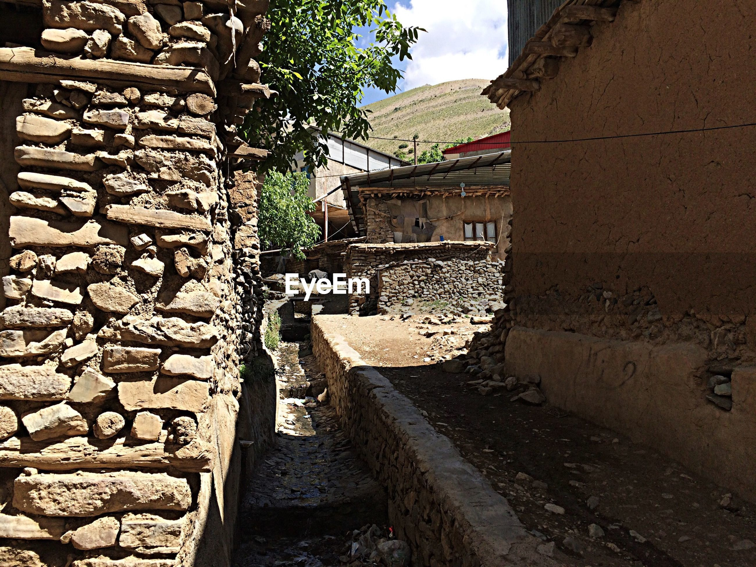 architecture, built structure, building exterior, stone wall, wall - building feature, brick wall, house, residential building, cobblestone, old, residential structure, sky, building, wall, day, the way forward, stone material, outdoors, street, stone - object