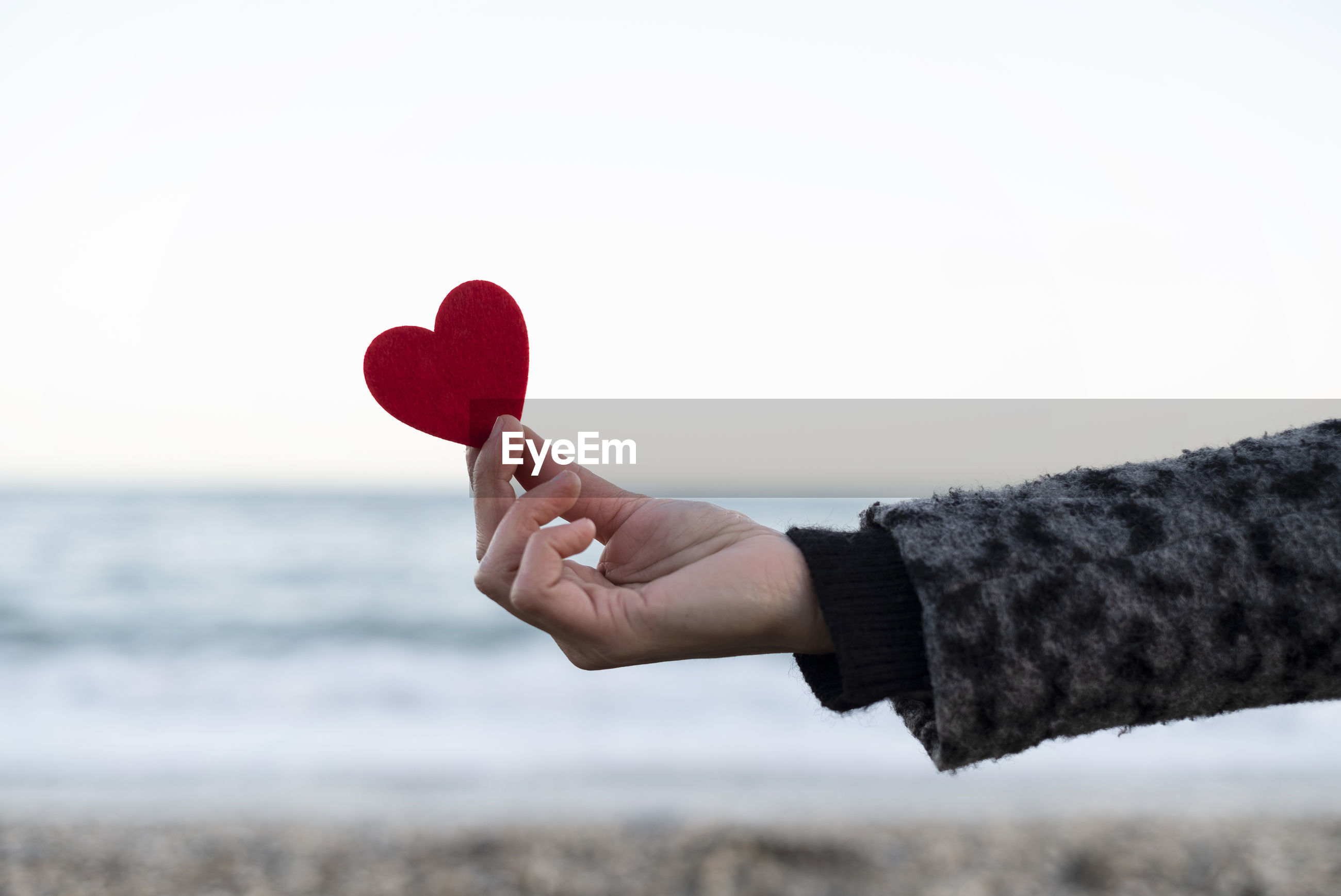 Cropped hand holding heart shape on beach