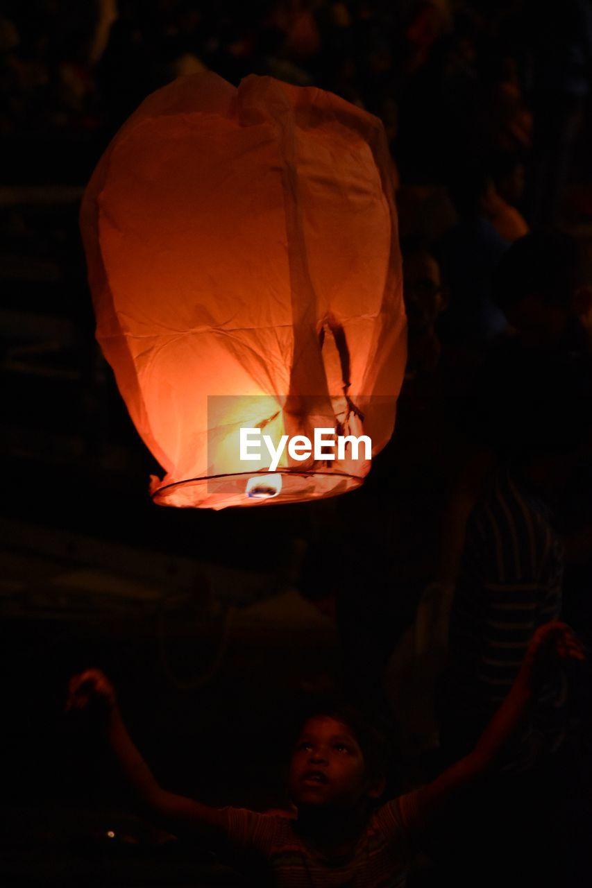lantern, illuminated, night, men, real people, lighting equipment, celebration, burning, paper lantern, glowing, group of people, orange color, incidental people, fire, people, flame, lifestyles, focus on foreground, chinese lantern