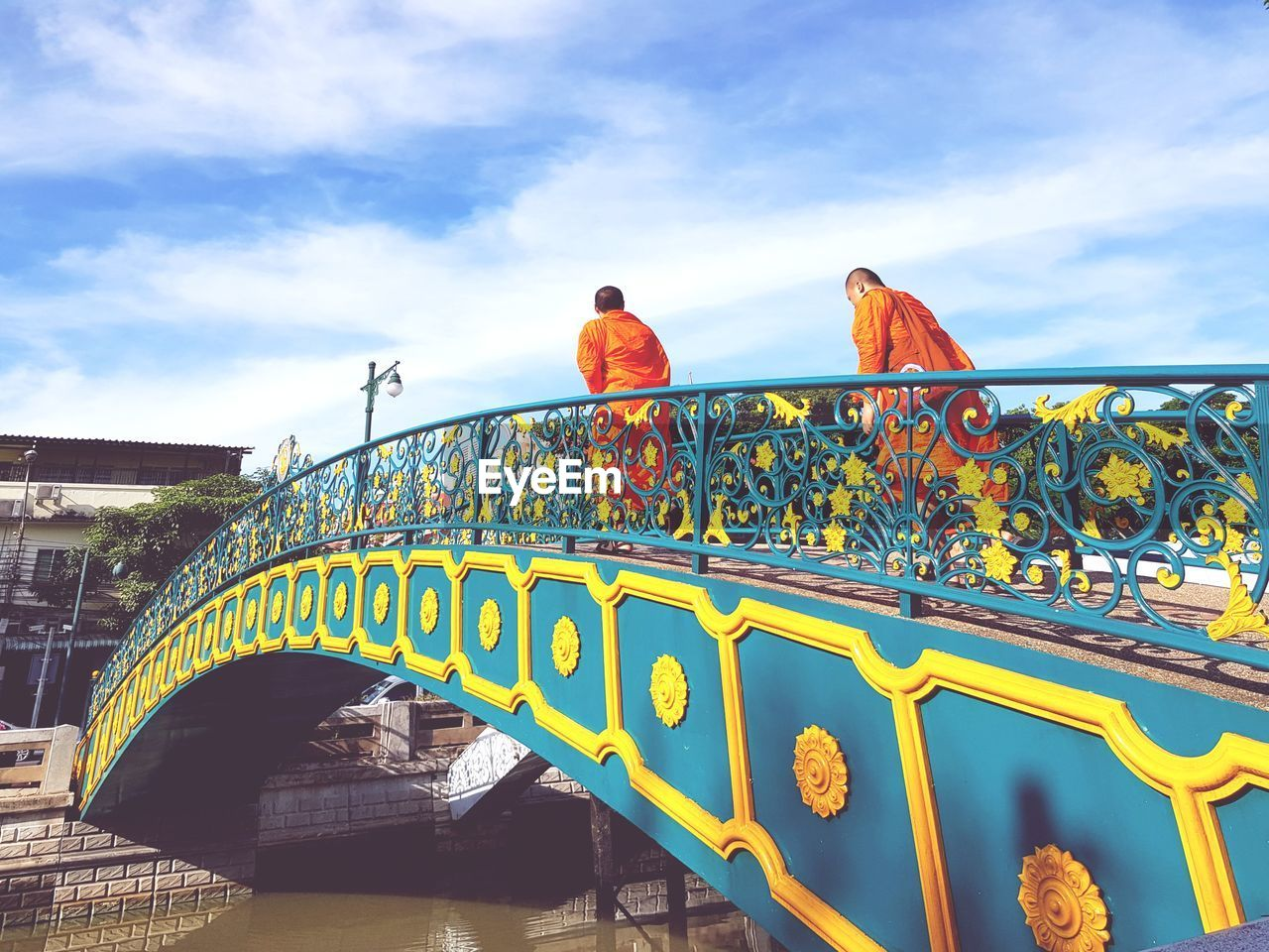 built structure, cloud - sky, bridge - man made structure, sky, architecture, low angle view, day, outdoors, travel destinations, red, real people, men, multi colored, building exterior, bird, nature, people