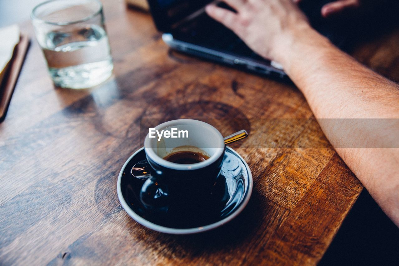 Close-Up Of Coffee Cup With Man Working On Laptop