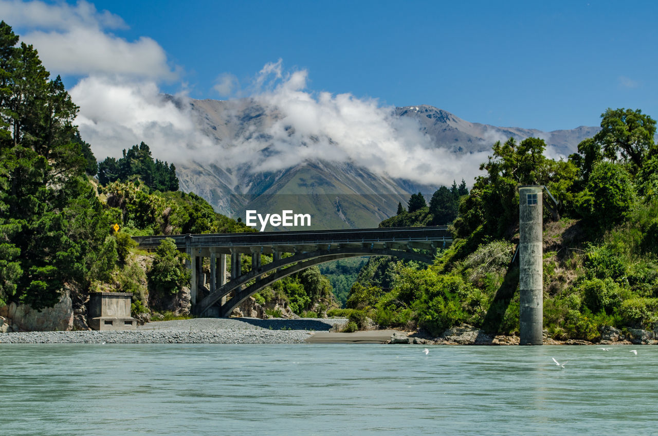 water, tree, sky, plant, built structure, bridge, mountain, scenics - nature, nature, architecture, bridge - man made structure, beauty in nature, river, waterfront, day, transportation, non-urban scene, connection, no people, outdoors, flowing water