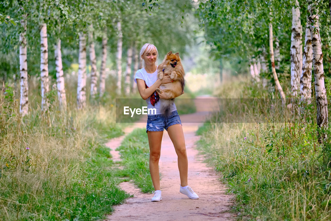plant, full length, women, leisure activity, lifestyles, young women, young adult, casual clothing, footpath, blond hair, grass, nature, smiling, adult, real people, land, tree, happiness, day, people, hair, shorts, outdoors, hairstyle