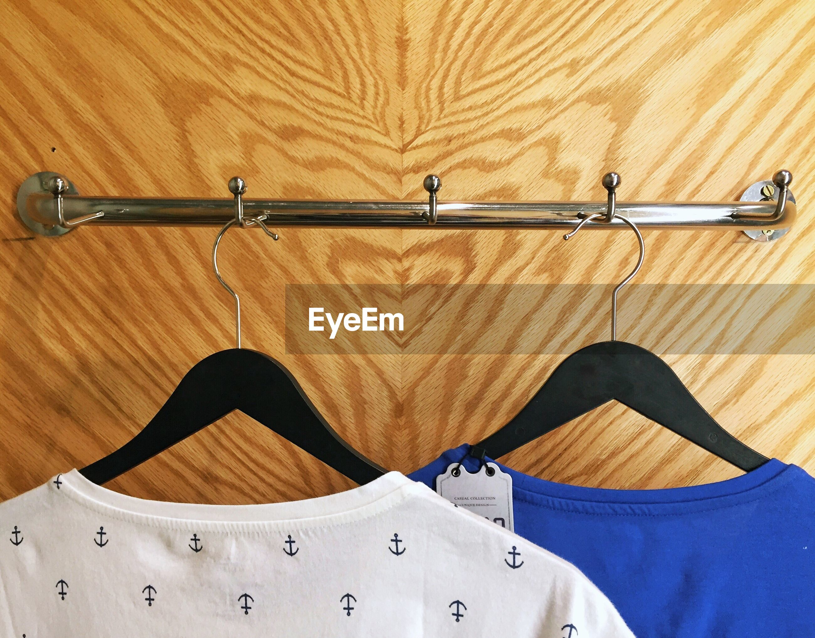 CLOSE-UP OF CLOTHES HANGING AGAINST WOOD
