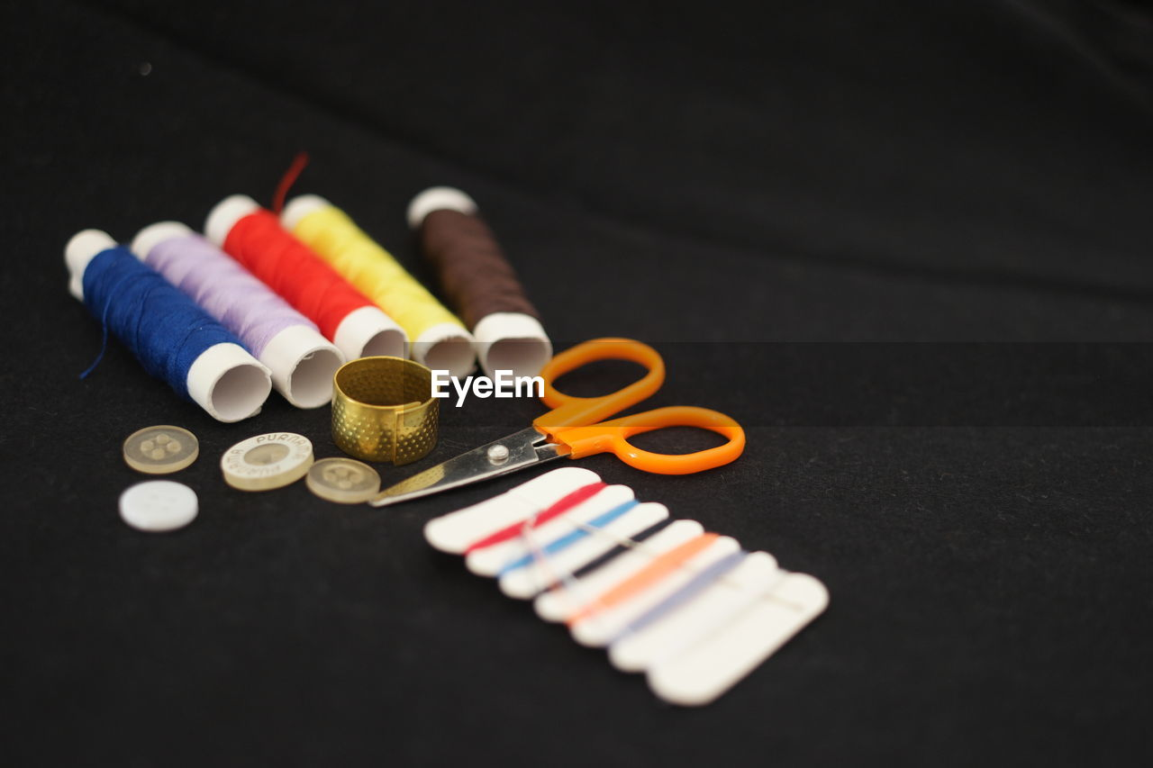 multi colored, still life, no people, indoors, selective focus, close-up, choice, variation, table, large group of objects, sewing item, high angle view, focus on foreground, orange color, thread, creativity, music, white color, art and craft, button, black background, art and craft equipment