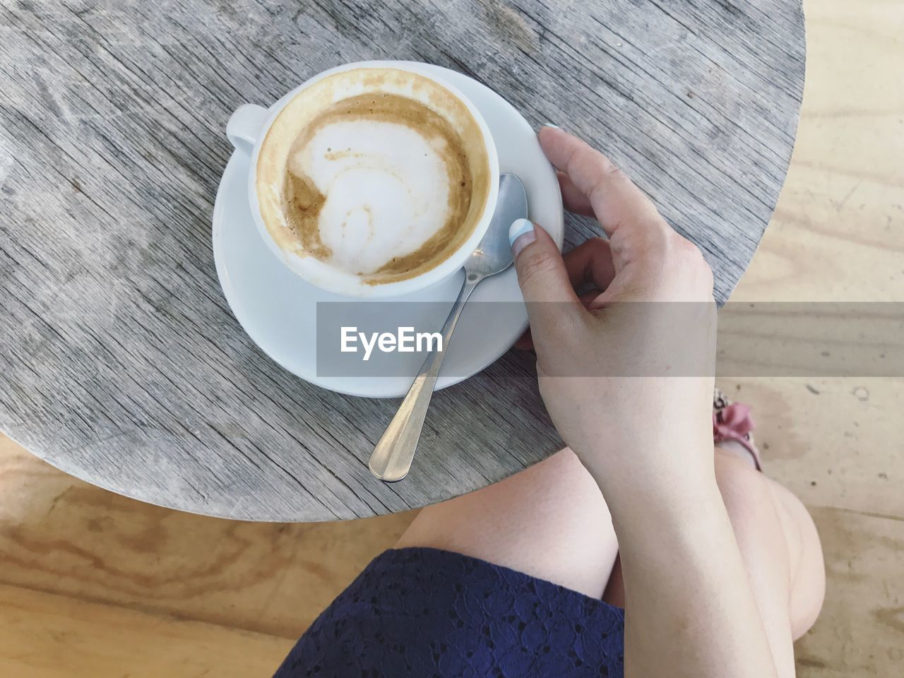 Low section of woman having coffee