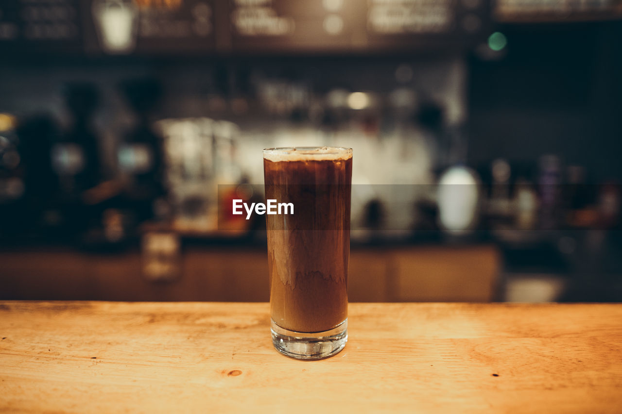 drink, refreshment, food and drink, glass, table, household equipment, drinking glass, alcohol, indoors, still life, focus on foreground, close-up, bar - drink establishment, freshness, wood - material, no people, coffee, coffee - drink, beer, brown, bar counter