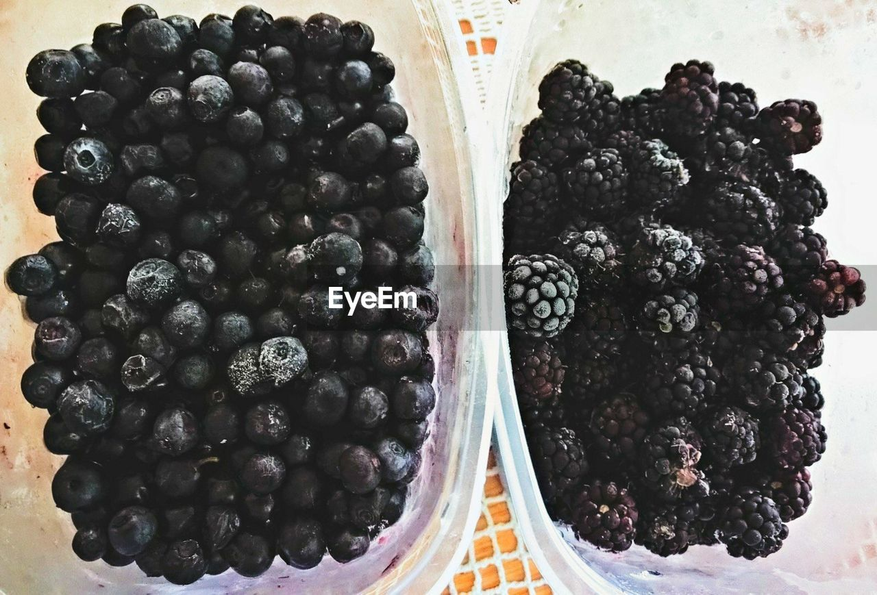 Close-up of blueberries and blackberries in containers on table