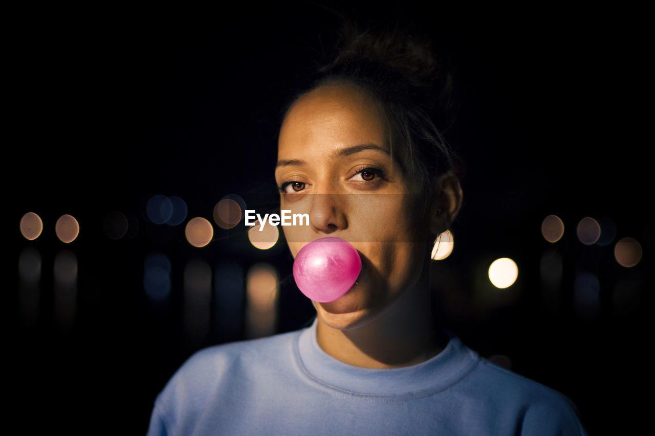 Close-Up Portrait Of Woman Blowing Bubble Gum