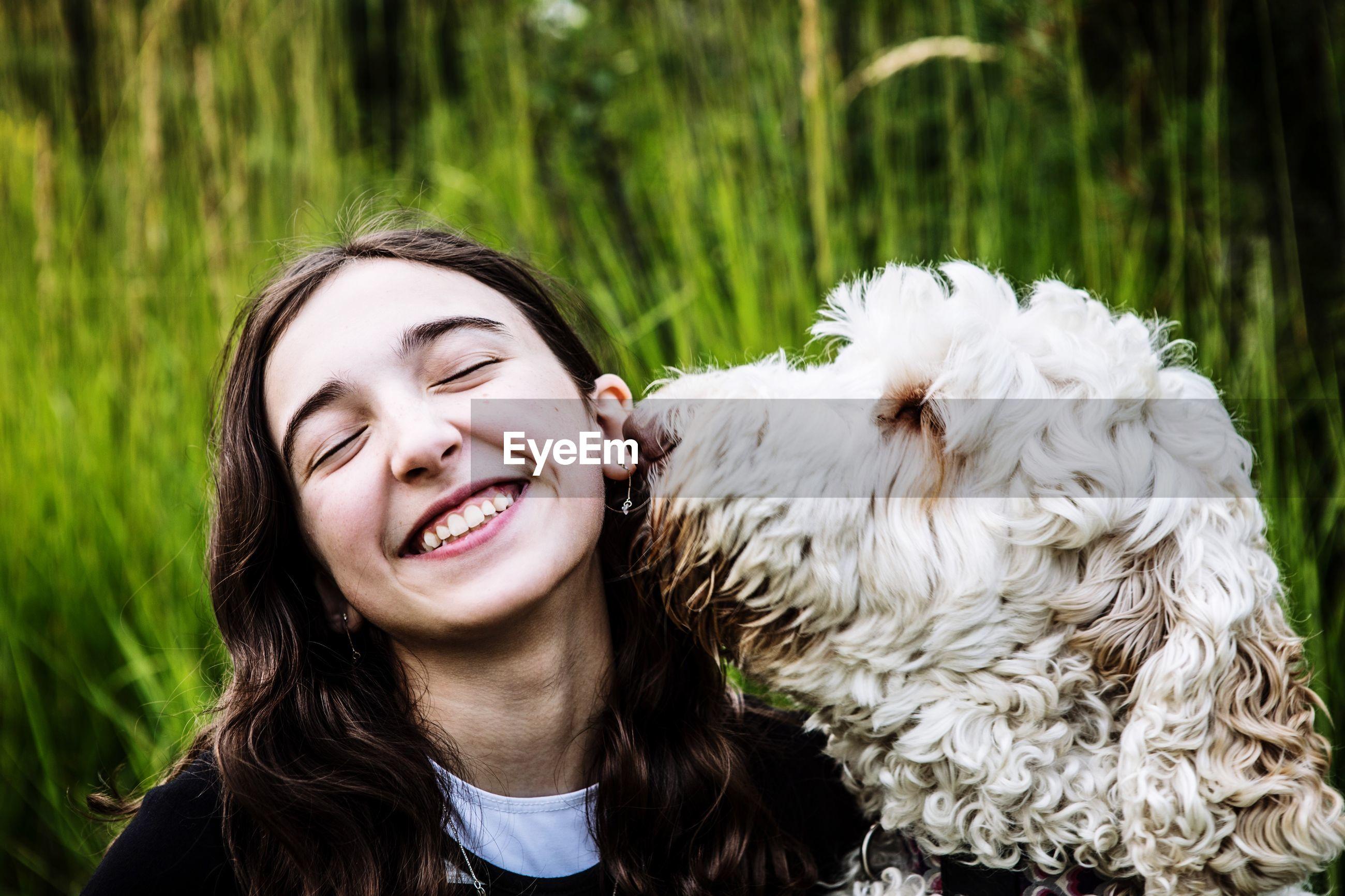 Smiling teenage girl with dog