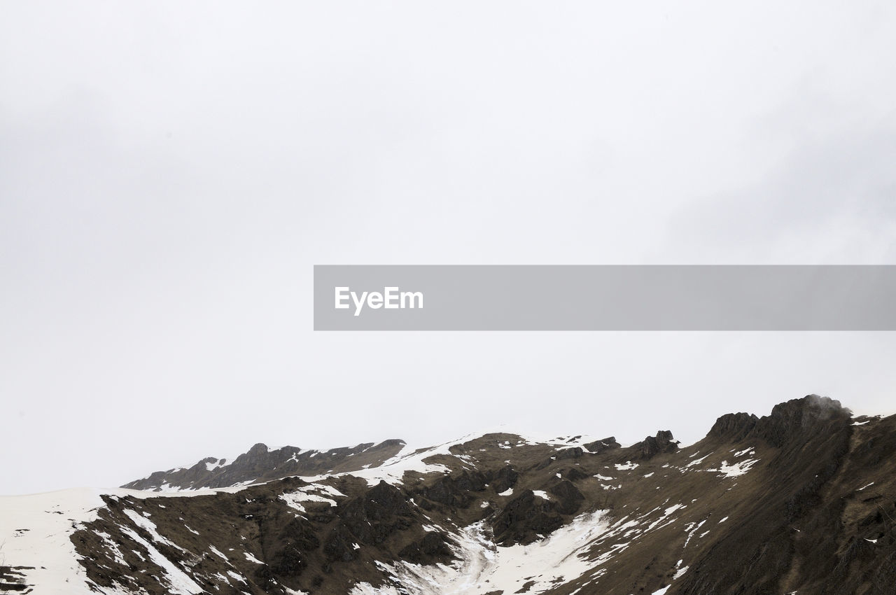 sky, beauty in nature, mountain, winter, snow, cold temperature, scenics - nature, tranquility, copy space, nature, tranquil scene, clear sky, day, no people, non-urban scene, environment, mountain range, rock, outdoors, mountain peak, snowcapped mountain