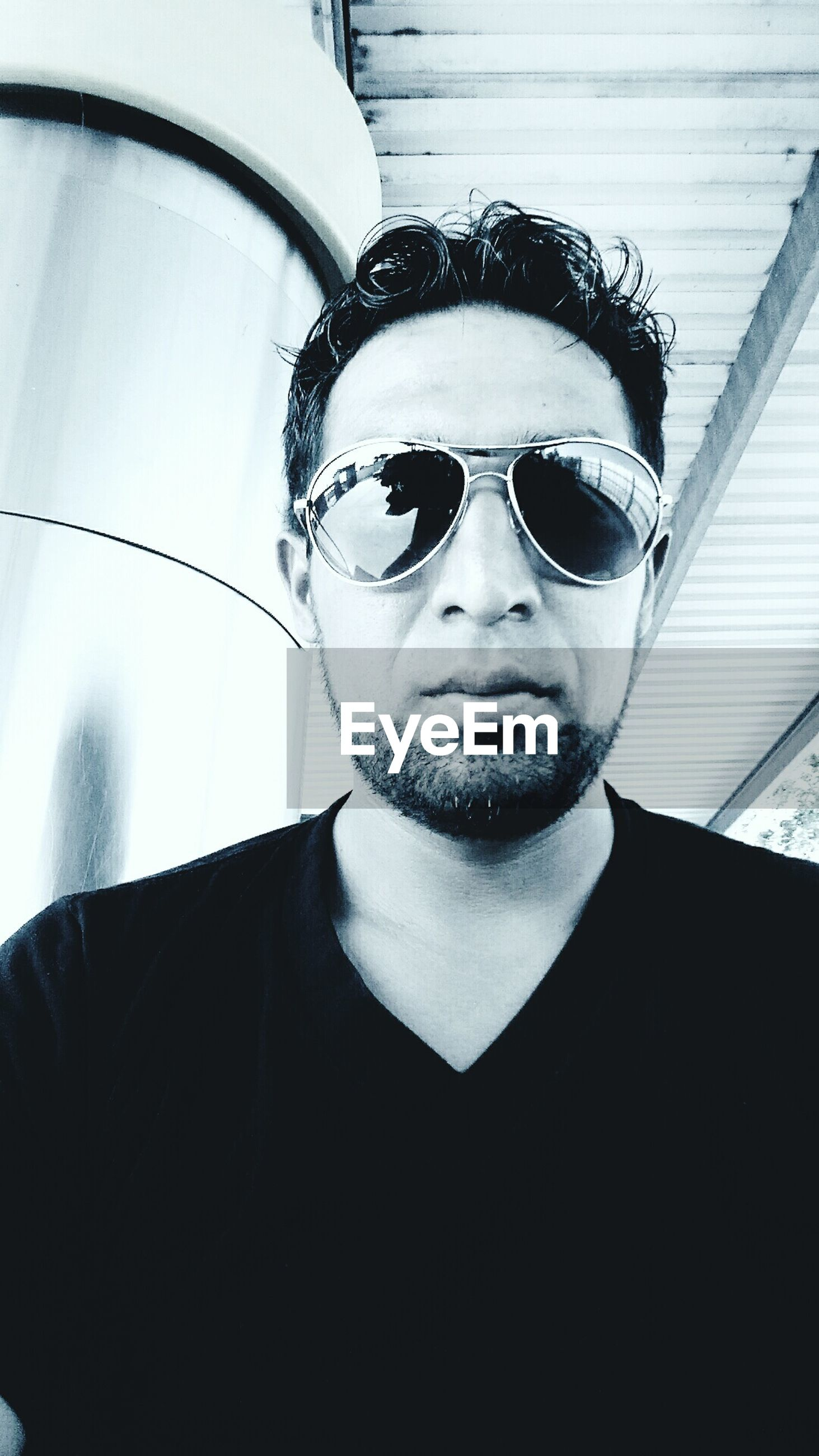 looking at camera, portrait, person, young adult, lifestyles, young men, front view, headshot, sunglasses, leisure activity, indoors, smiling, mid adult, casual clothing, head and shoulders, mid adult men, reflection, close-up