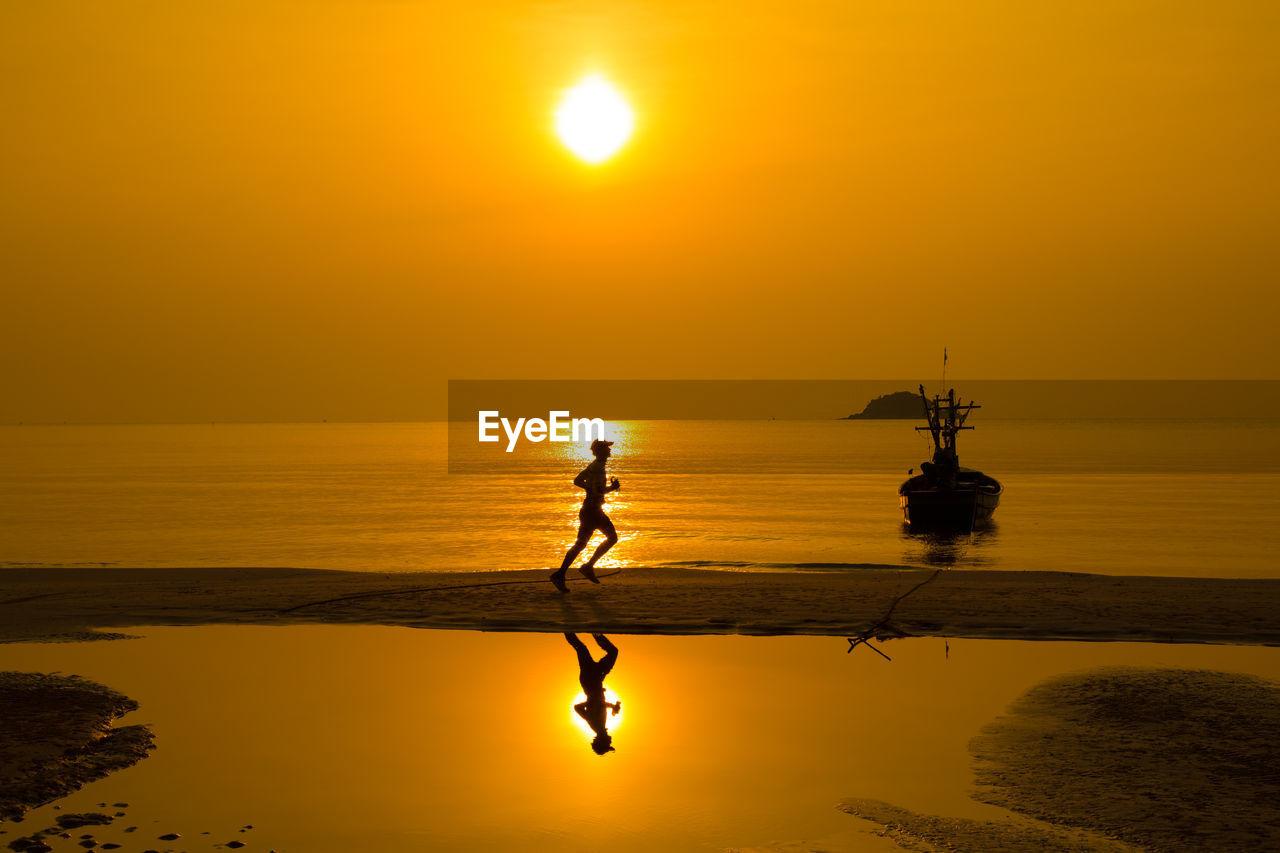 SILHOUETTE MAN STANDING BY SEA AGAINST ORANGE SKY