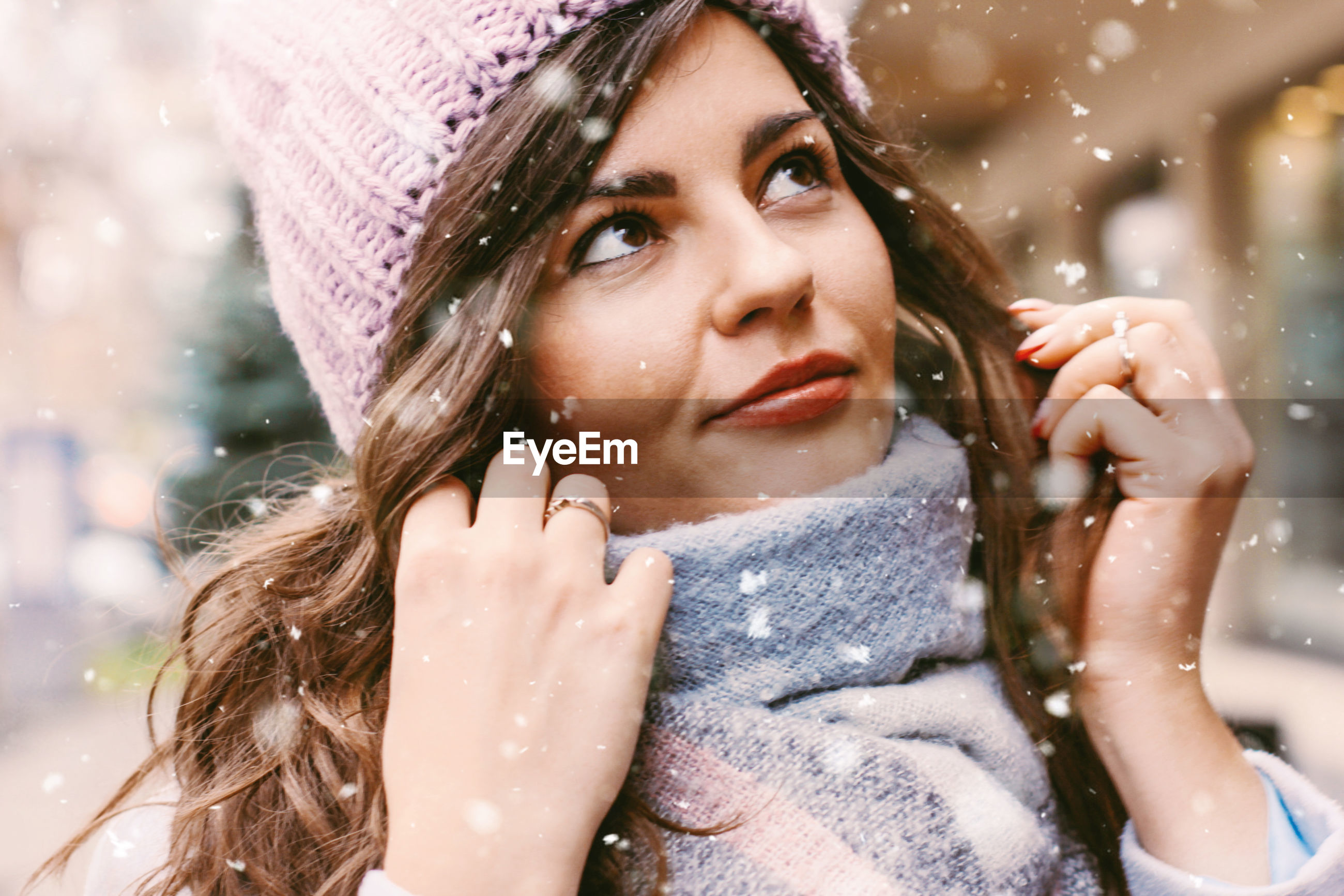 Close-up of young woman looking away while standing outdoors during snowfall