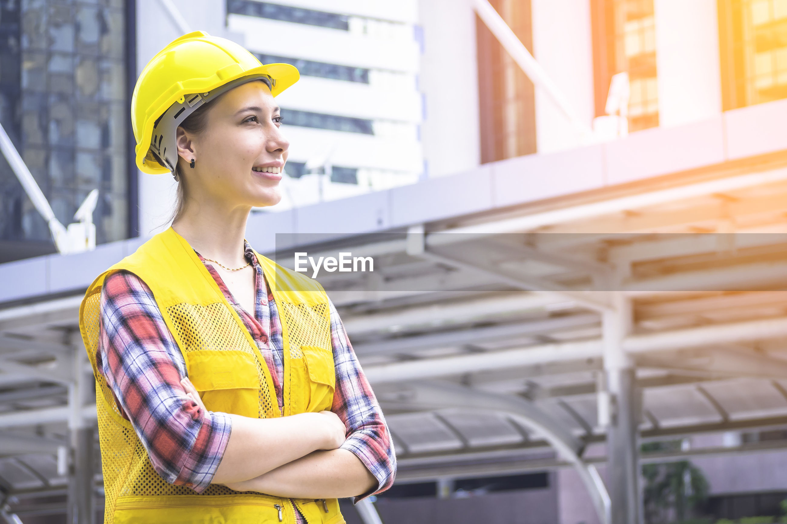 Smiling young engineer standing against buildings in city