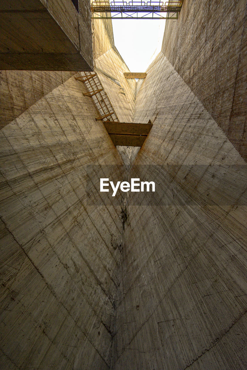 architecture, built structure, no people, indoors, pattern, day, wood - material, sunlight, high angle view, wall - building feature, building, staircase, nature, railing, lighting equipment, flooring, steps and staircases, ceiling, directly below, concrete