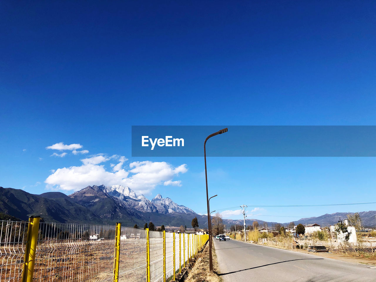 sky, mountain, blue, road, scenics - nature, nature, street light, street, mountain range, beauty in nature, barrier, transportation, no people, tranquility, tranquil scene, the way forward, direction, fence, day, copy space, outdoors, snowcapped mountain