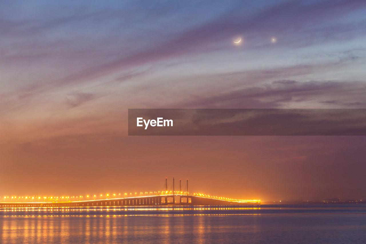 Illuminated Bridge Over Sea Against Cloudy Sky At Night