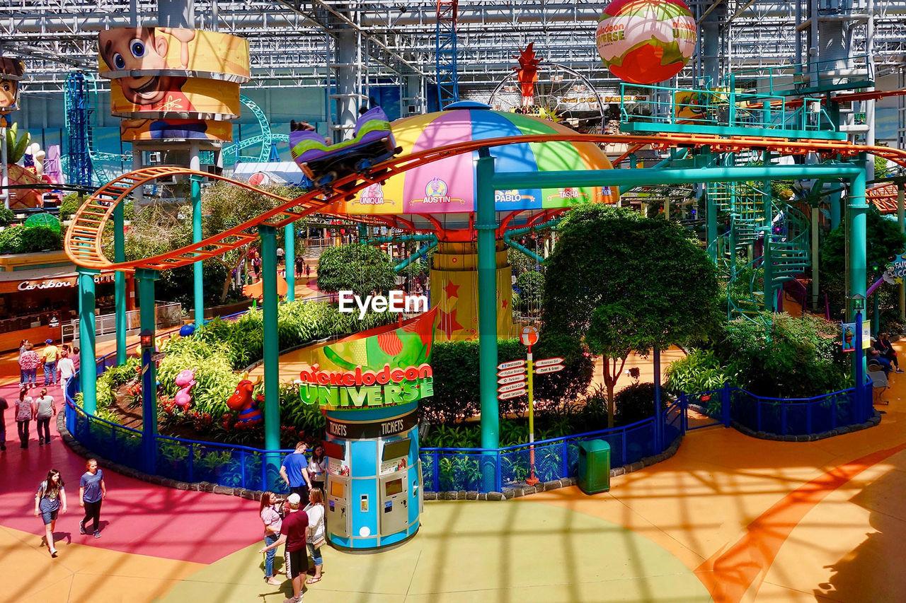 amusement park, amusement park ride, architecture, built structure, arts culture and entertainment, day, incidental people, building exterior, plant, nature, tree, multi colored, enjoyment, carousel, outdoors, city, fun, real people, sunlight