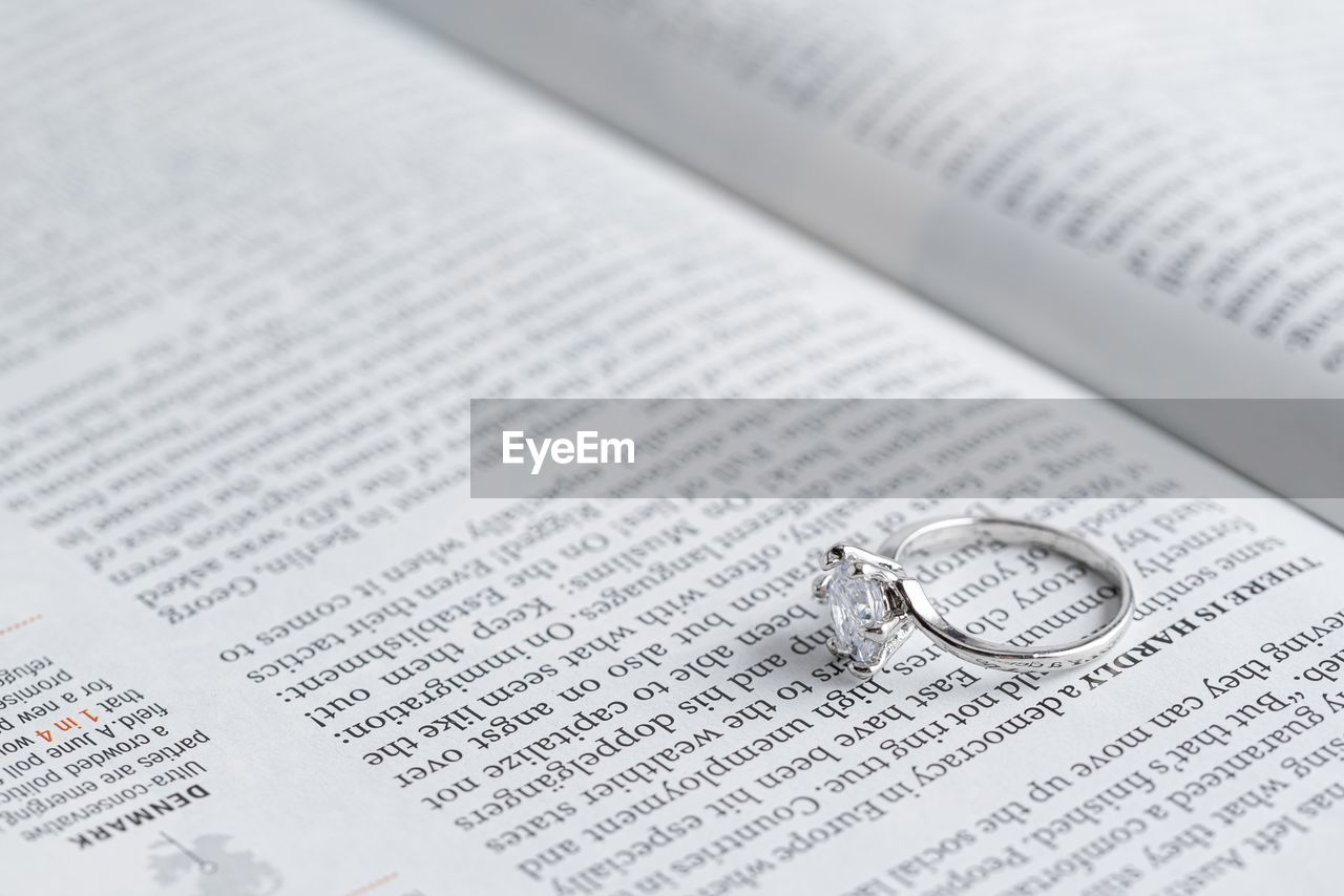 publication, text, ring, book, still life, jewelry, close-up, indoors, paper, western script, wedding, wealth, no people, high angle view, wedding ring, event, page, emotion, communication, selective focus