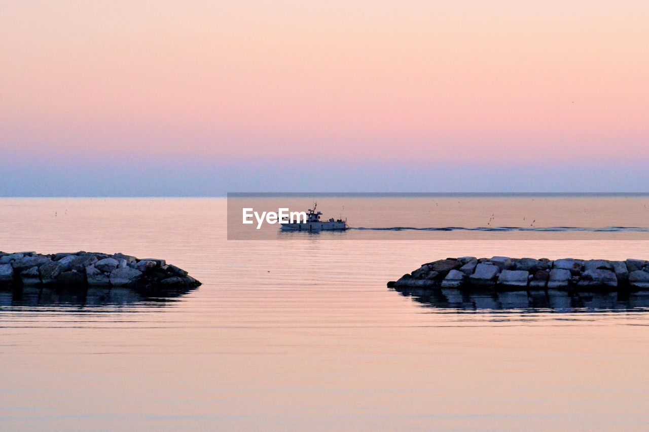 sea, water, beauty in nature, tranquility, sunset, nature, tranquil scene, rock - object, scenics, horizon over water, reflection, outdoors, no people, sky, beach, groyne, clear sky, day