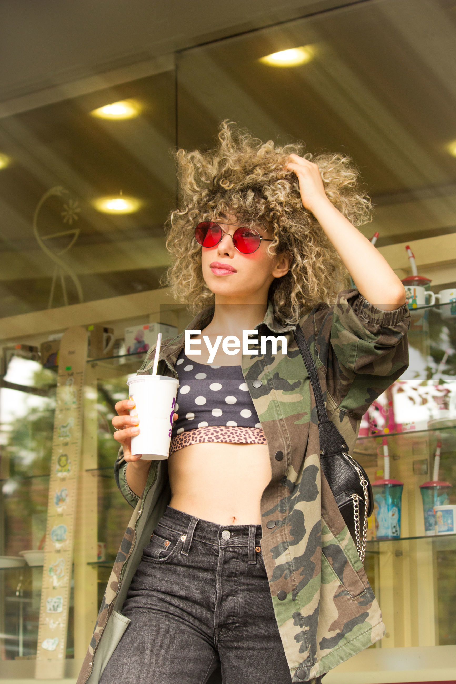 Young woman holding drink while standing against store