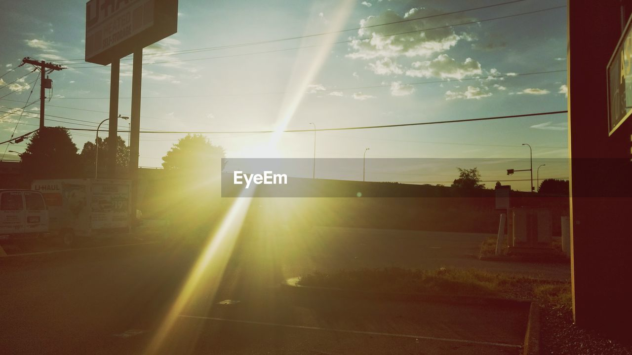 sunbeam, lens flare, sun, sunlight, no people, sky, power line, tree, outdoors, road, cable, sunset, day, nature, electricity pylon, architecture, building exterior, city