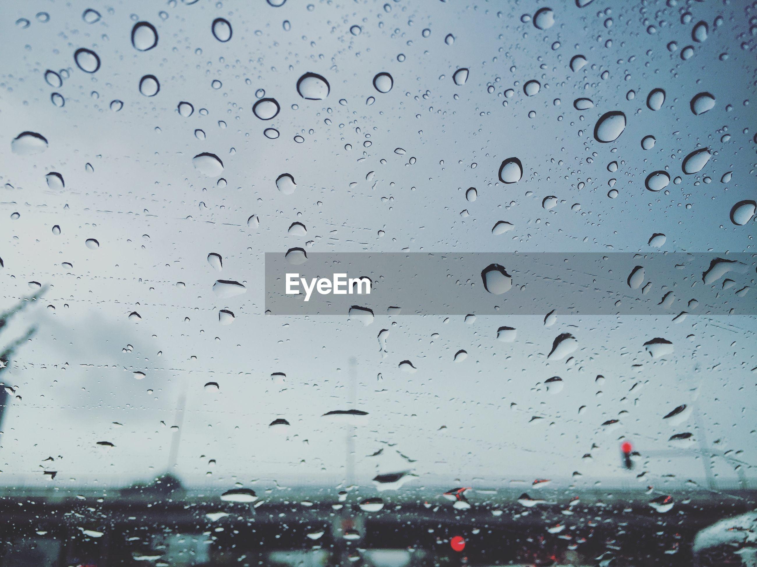 Full frame shot of wet glass windshield with raindrops against sky