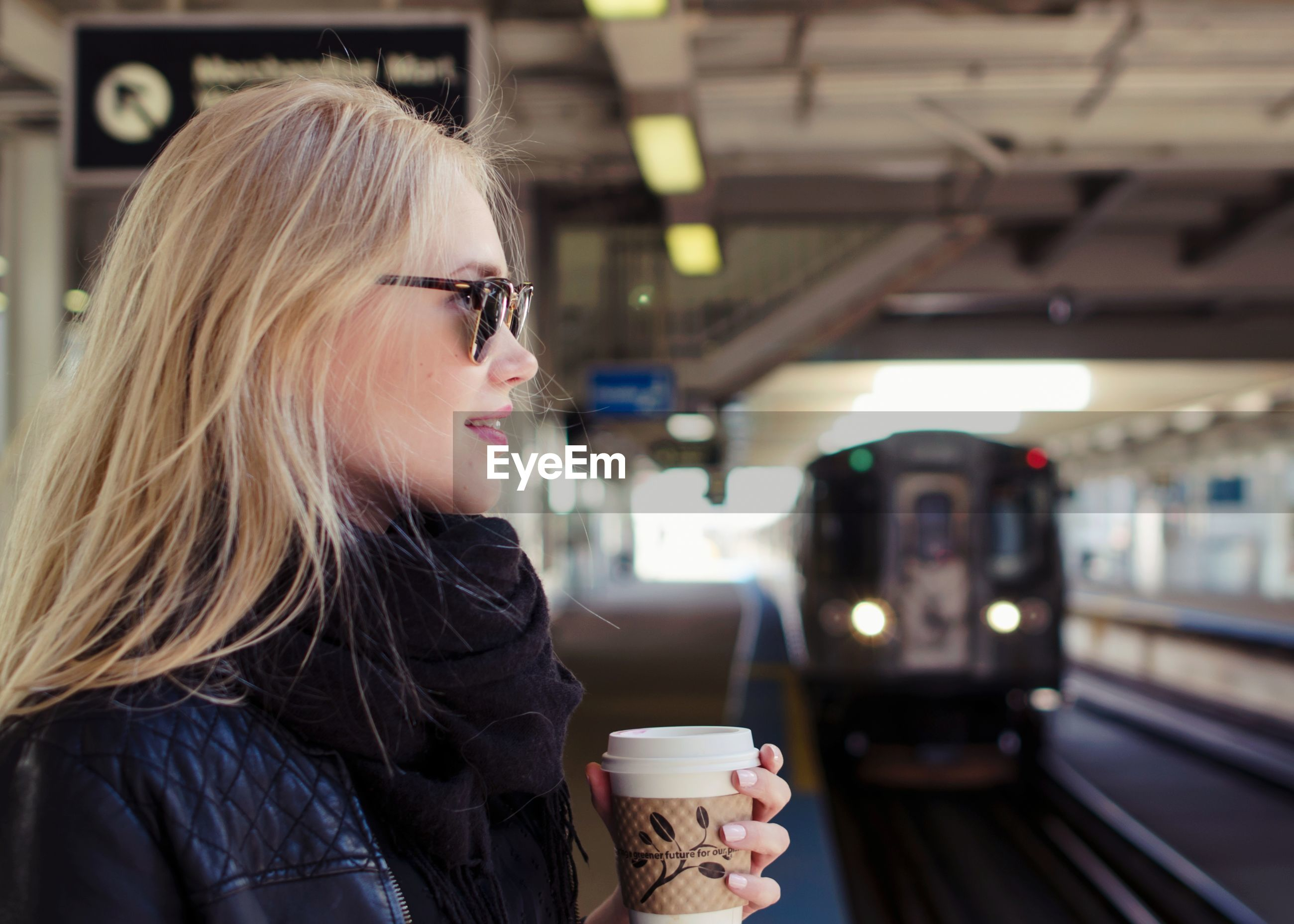 Woman holding coffee cup in city