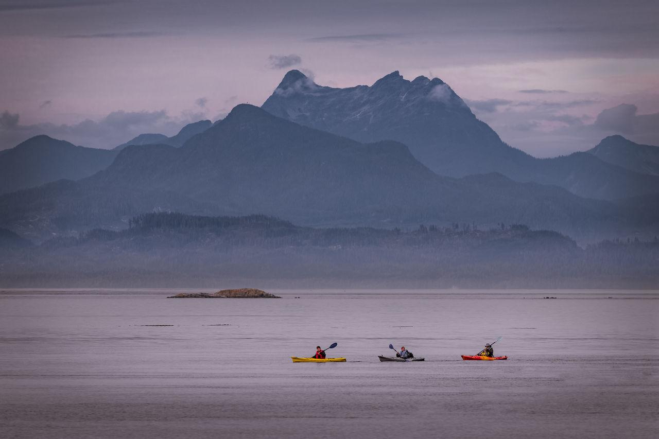 People Kayaking In Lake Against Mountains During Winter