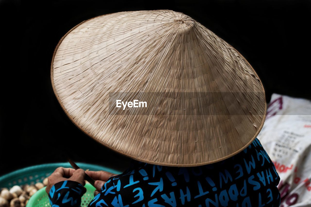 Rear View Of Market Vendor Wearing Asian Style Conical Hat