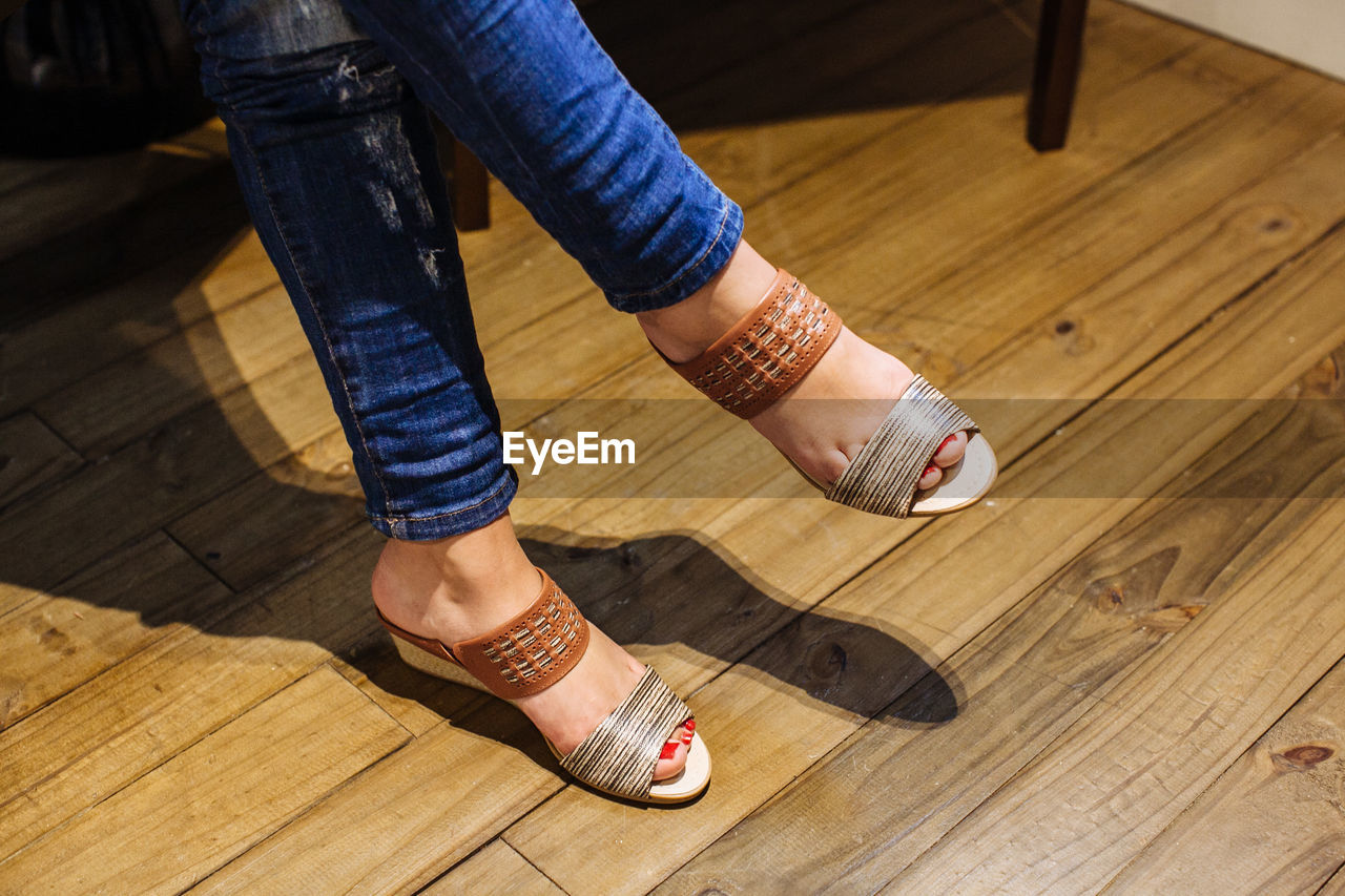 Low section of woman wearing sandals on hardwood floor