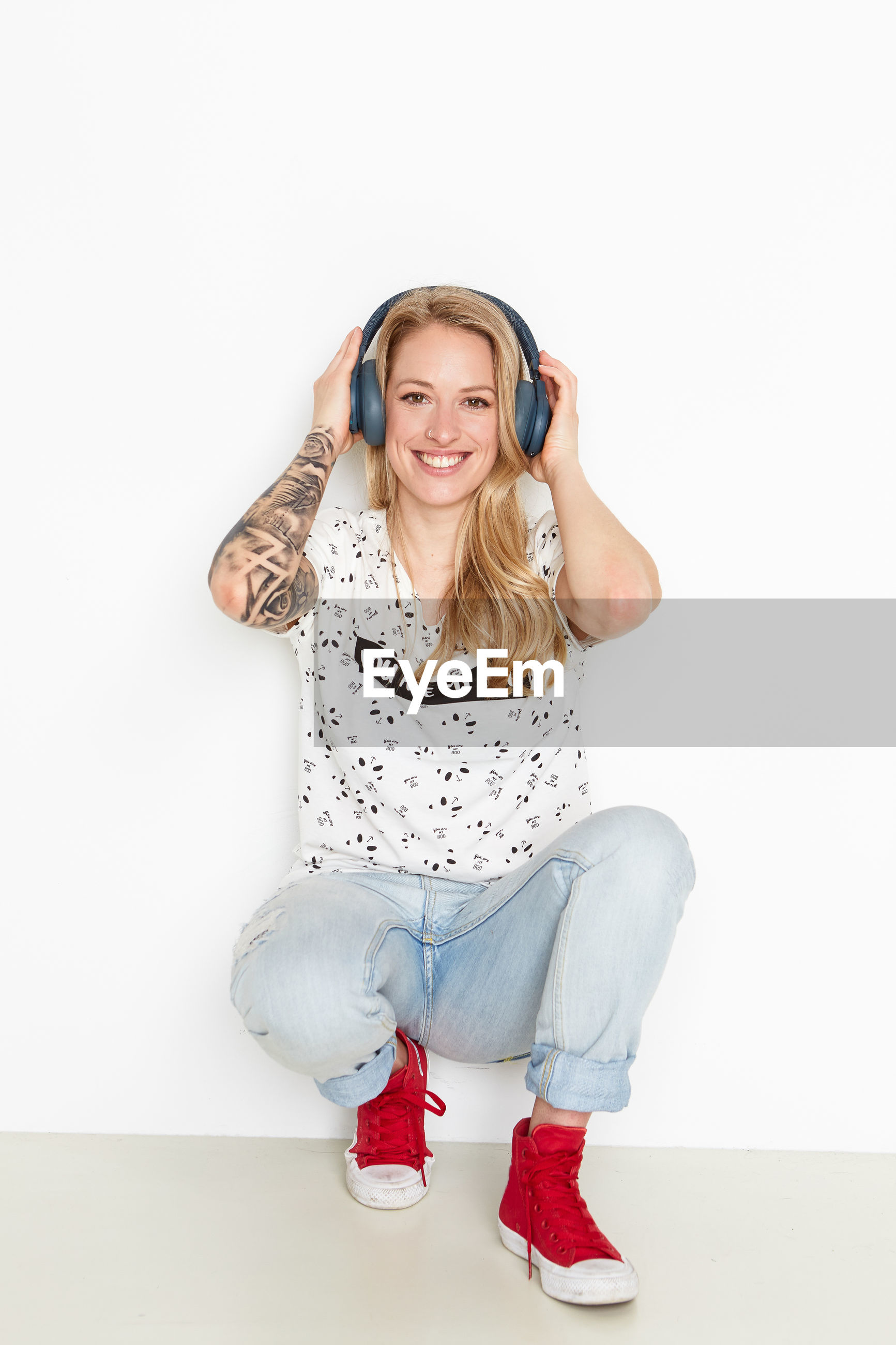 Portrait of smiling woman holding headphones while crouching against wall
