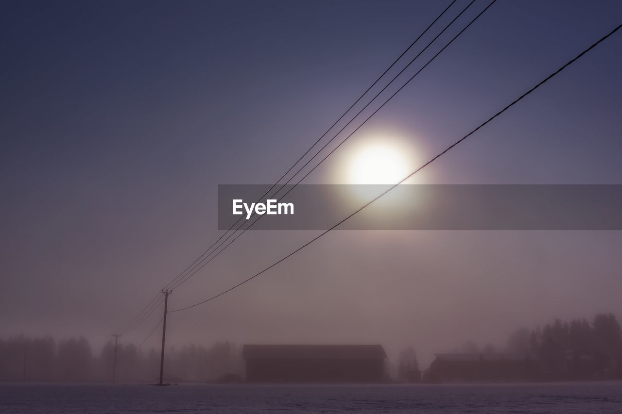 Silhouette Power Lines Against Sky During Sunset In Foggy Weather