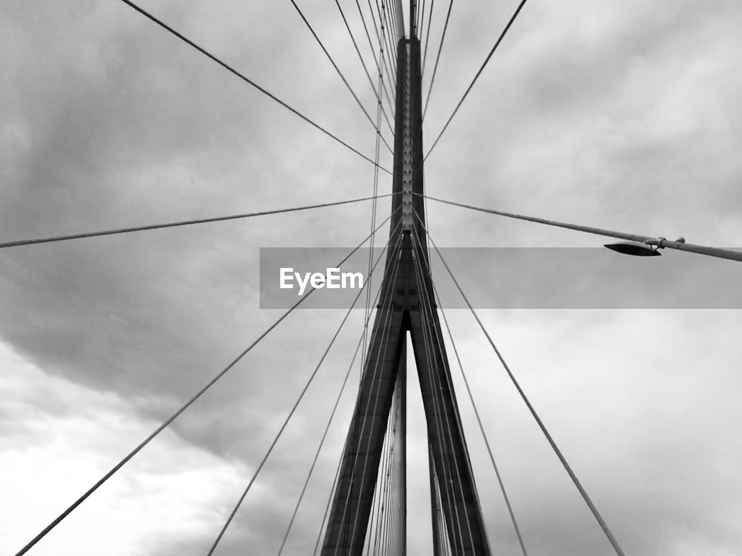 Directly below shot cable-stayed bridge against cloudy sky