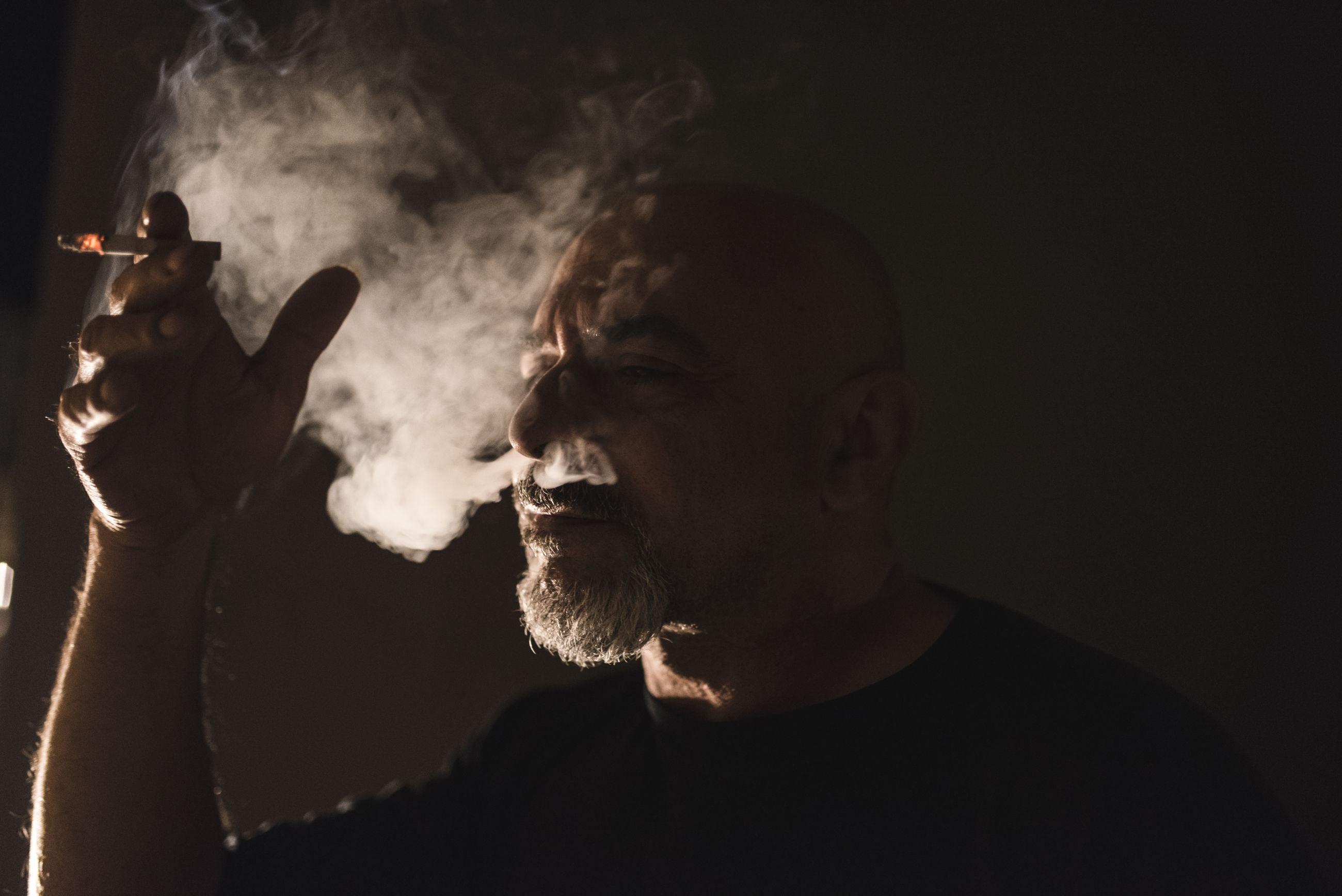 Mature man smoking cigarette at home