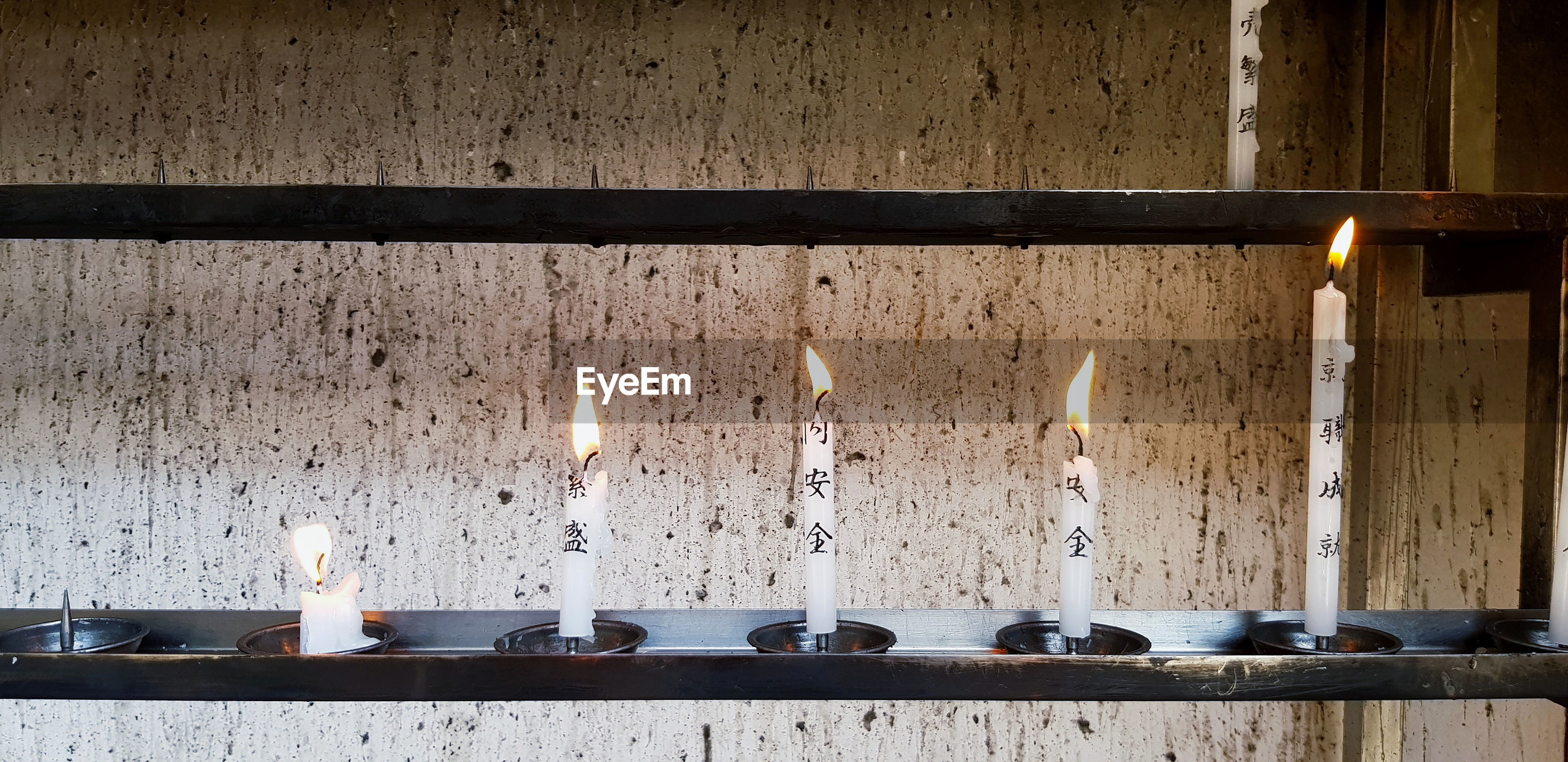 View of candles on table against wall in japanese temple
