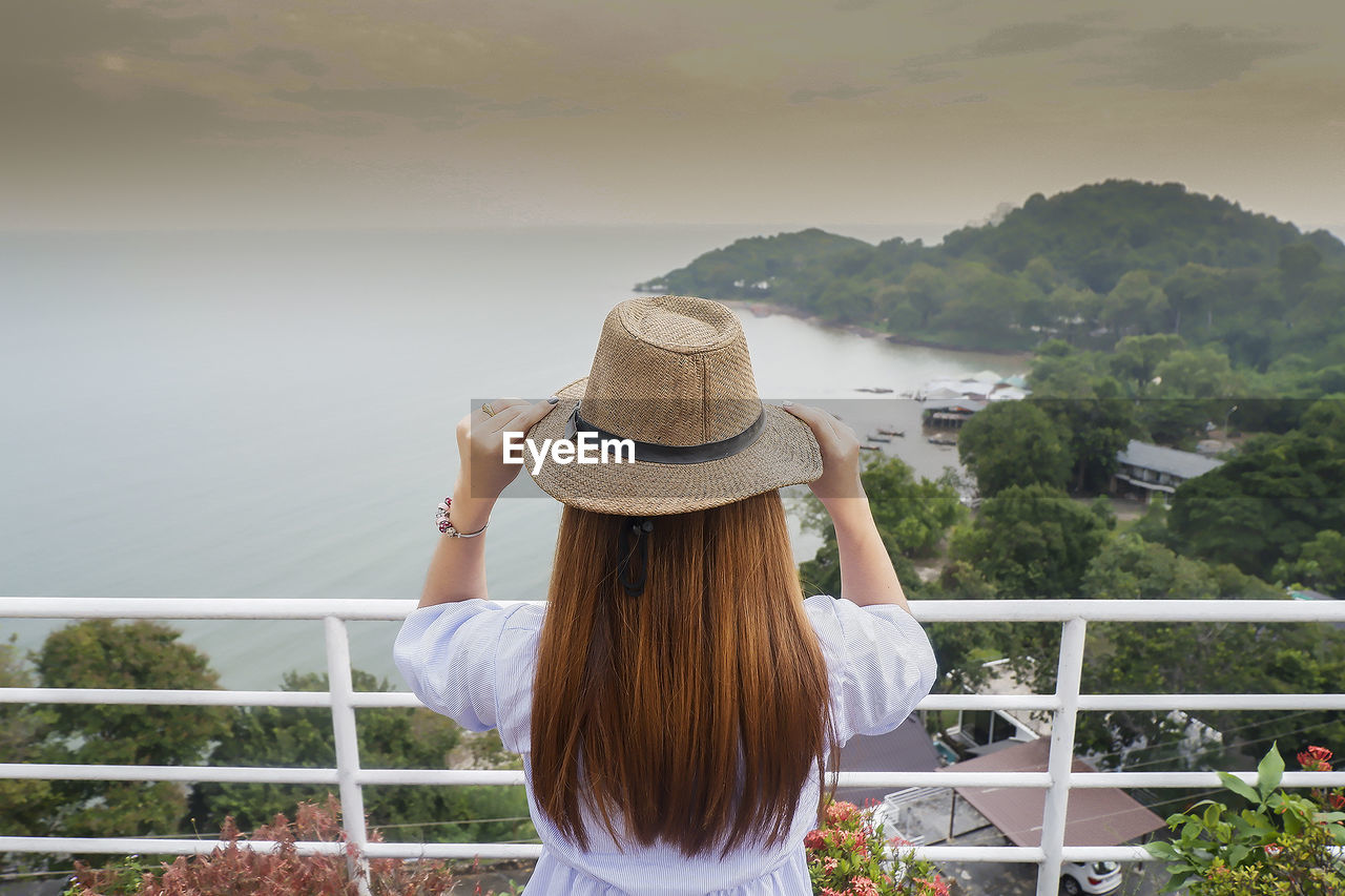Rear view of woman wearing hat while looking at sea during sunset