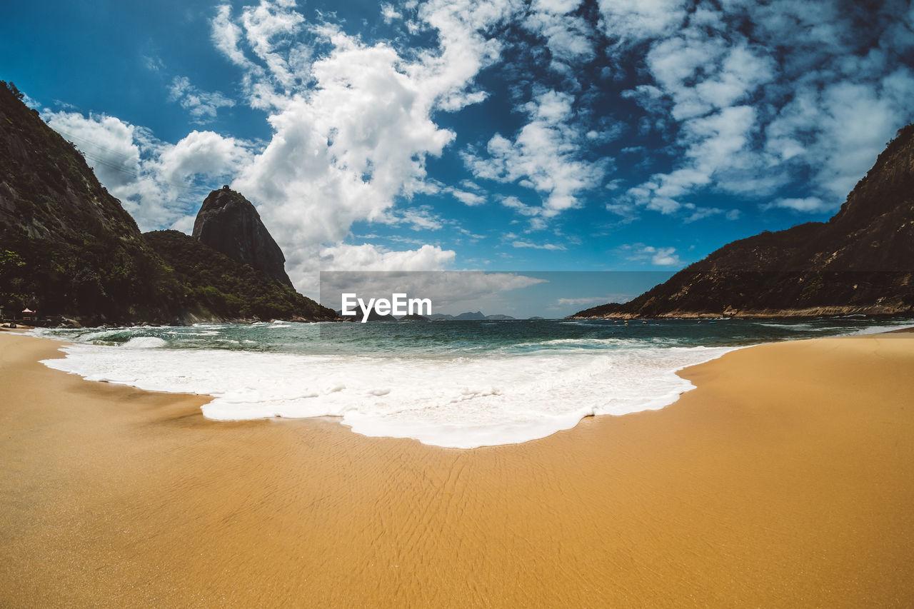 View Of Calm Beach Against Cloudy Sky