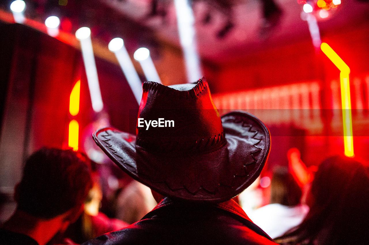 Rear View Of Man Wearing Cowboy Hat At Nightclub