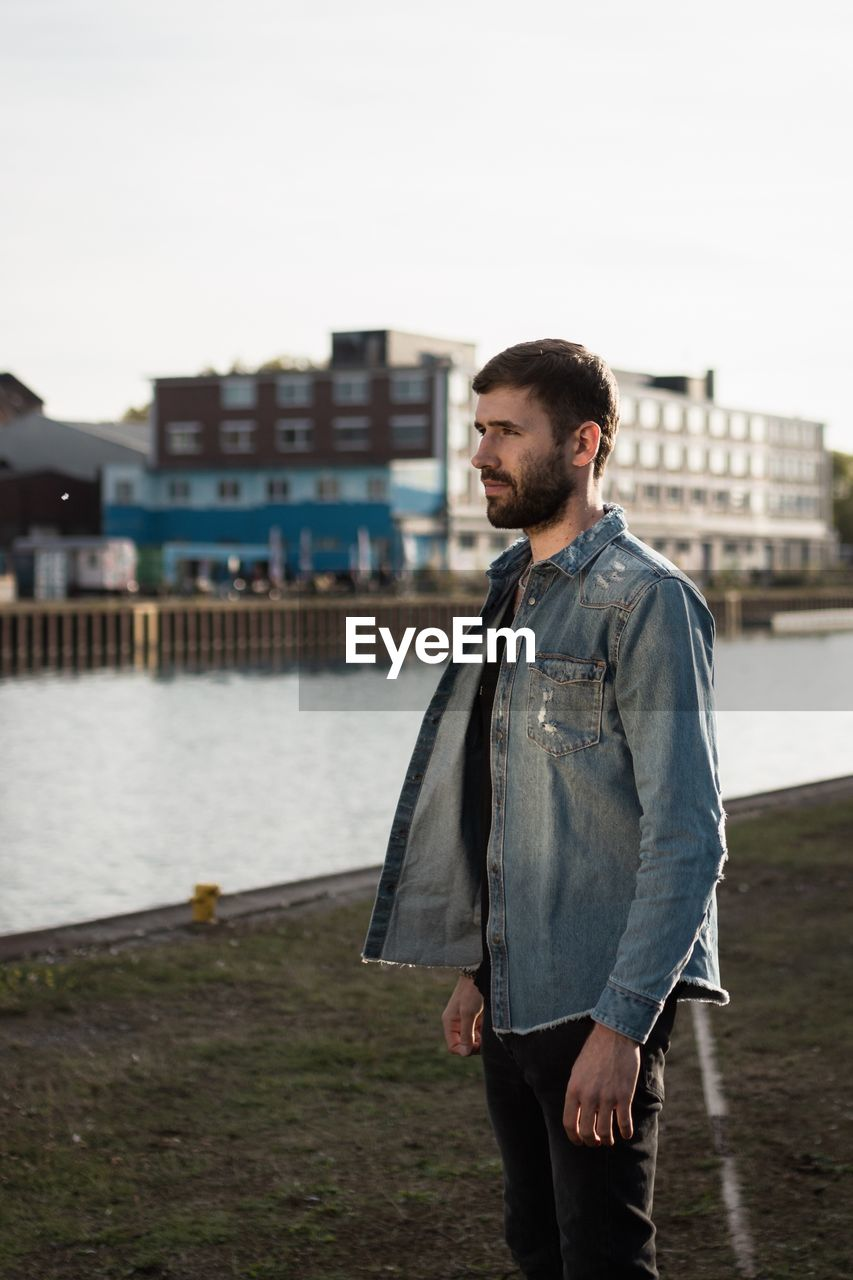 standing, architecture, one person, built structure, casual clothing, young adult, water, three quarter length, young men, building exterior, real people, looking away, focus on foreground, beard, nature, facial hair, sky, leisure activity, outdoors, contemplation, jeans
