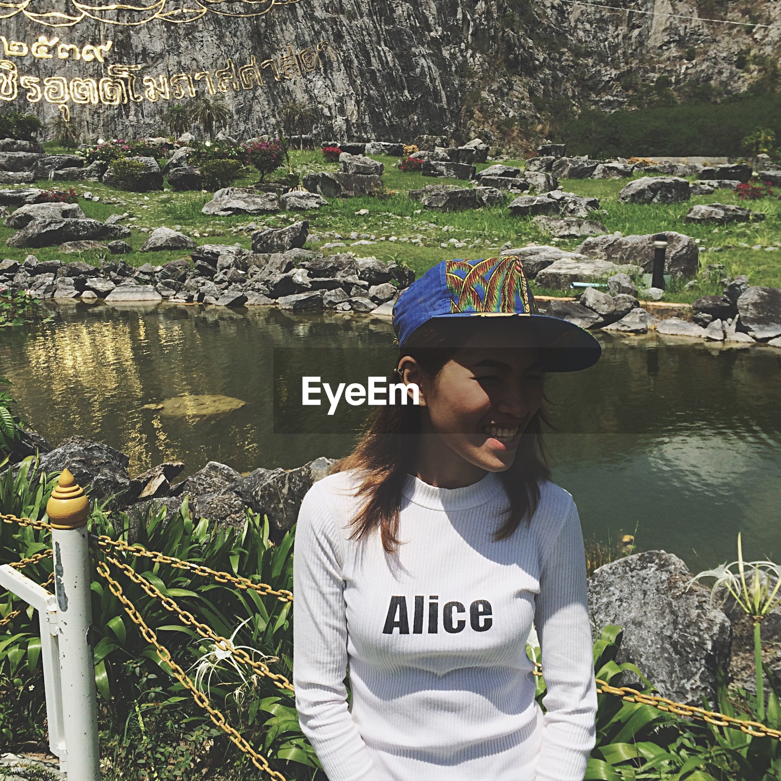 water, lifestyles, leisure activity, casual clothing, lake, standing, person, river, communication, young adult, waist up, day, rear view, nature, text, sitting, outdoors, three quarter length