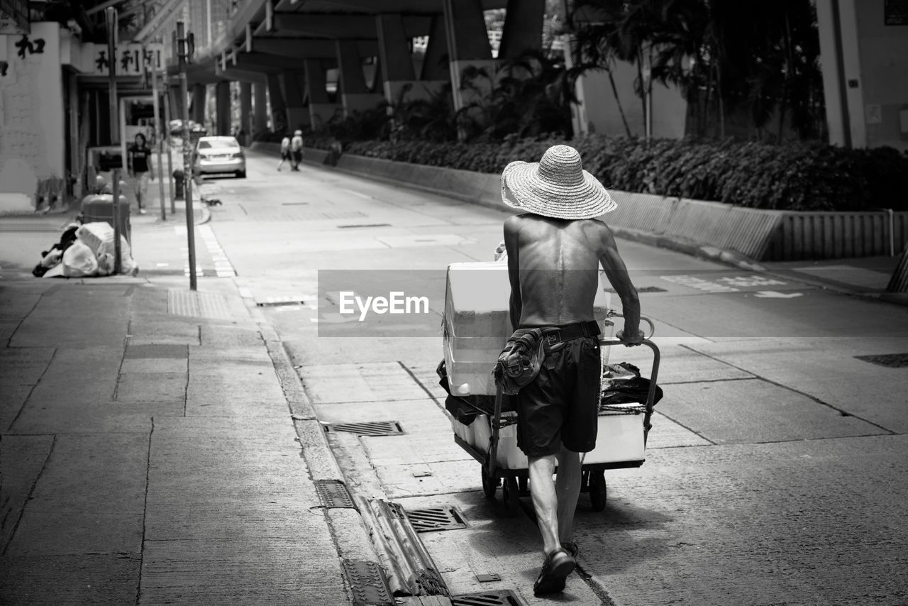 real people, rear view, hat, one person, city, full length, street, sitting, architecture, day, incidental people, clothing, lifestyles, walking, women, leisure activity, men, built structure, building exterior, outdoors