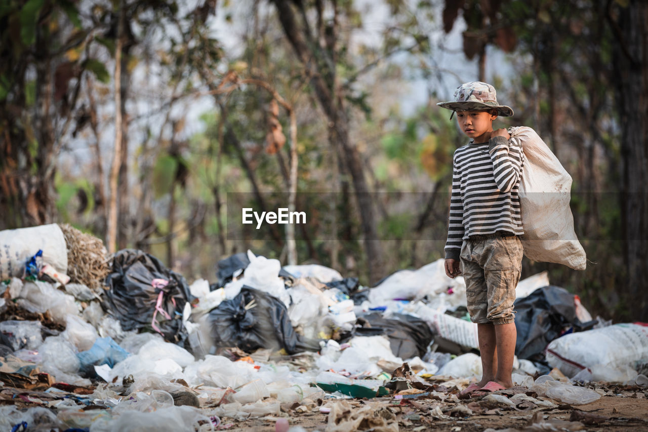 Boy holding plastic bag while standing at dump yard