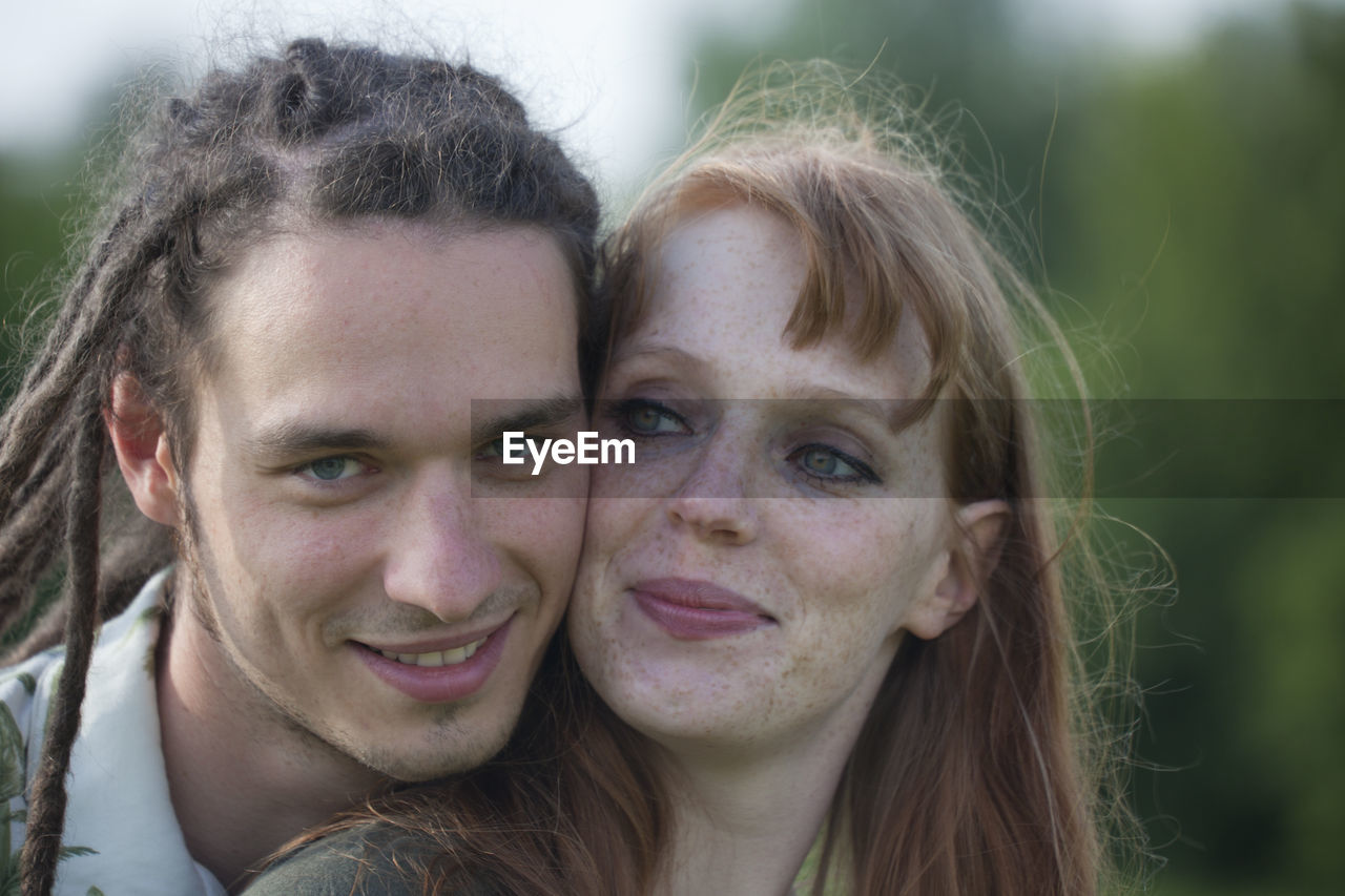 Close-up portrait of man with woman outdoors