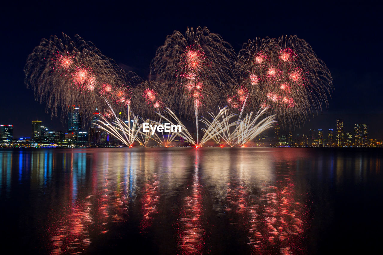 night, illuminated, water, reflection, firework, firework display, celebration, architecture, built structure, waterfront, arts culture and entertainment, river, nature, exploding, glowing, sky, event, motion, no people, light, bridge - man made structure, firework - man made object, outdoors, sparks, cityscape