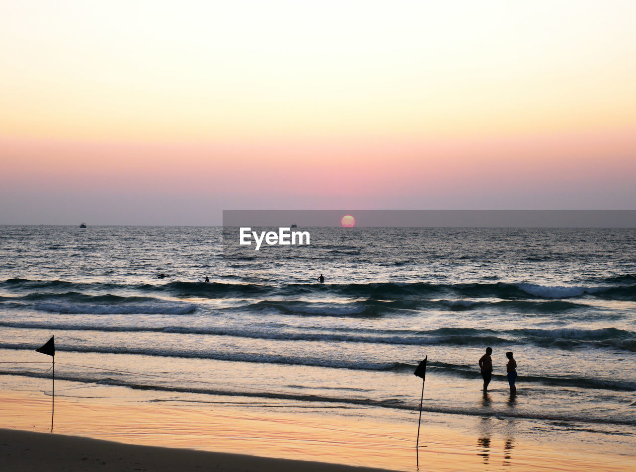 sea, sky, water, sunset, horizon over water, beach, scenics - nature, horizon, beauty in nature, land, orange color, wave, motion, nature, real people, clear sky, lifestyles, idyllic, people, outdoors