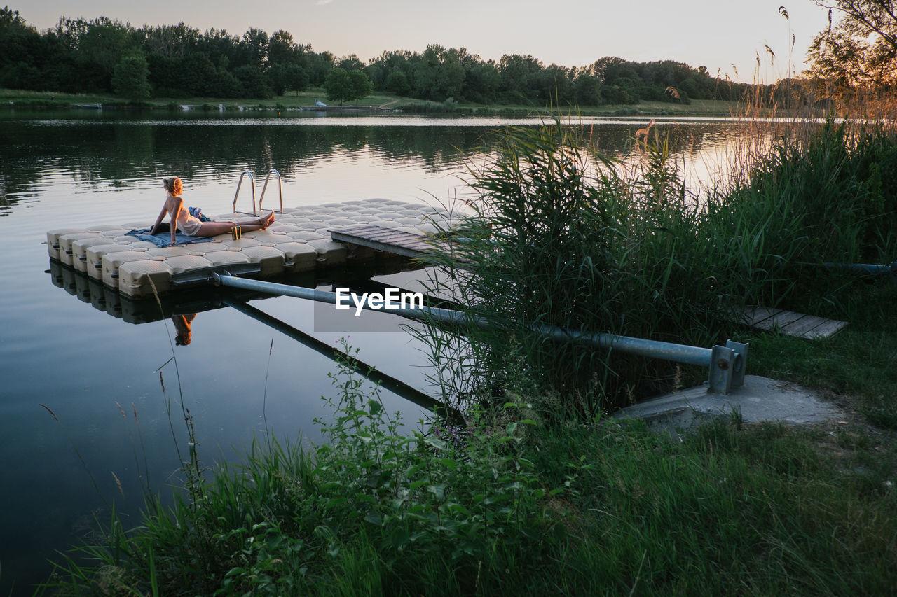 Woman Resting On Floating Platform In Lake During Sunset